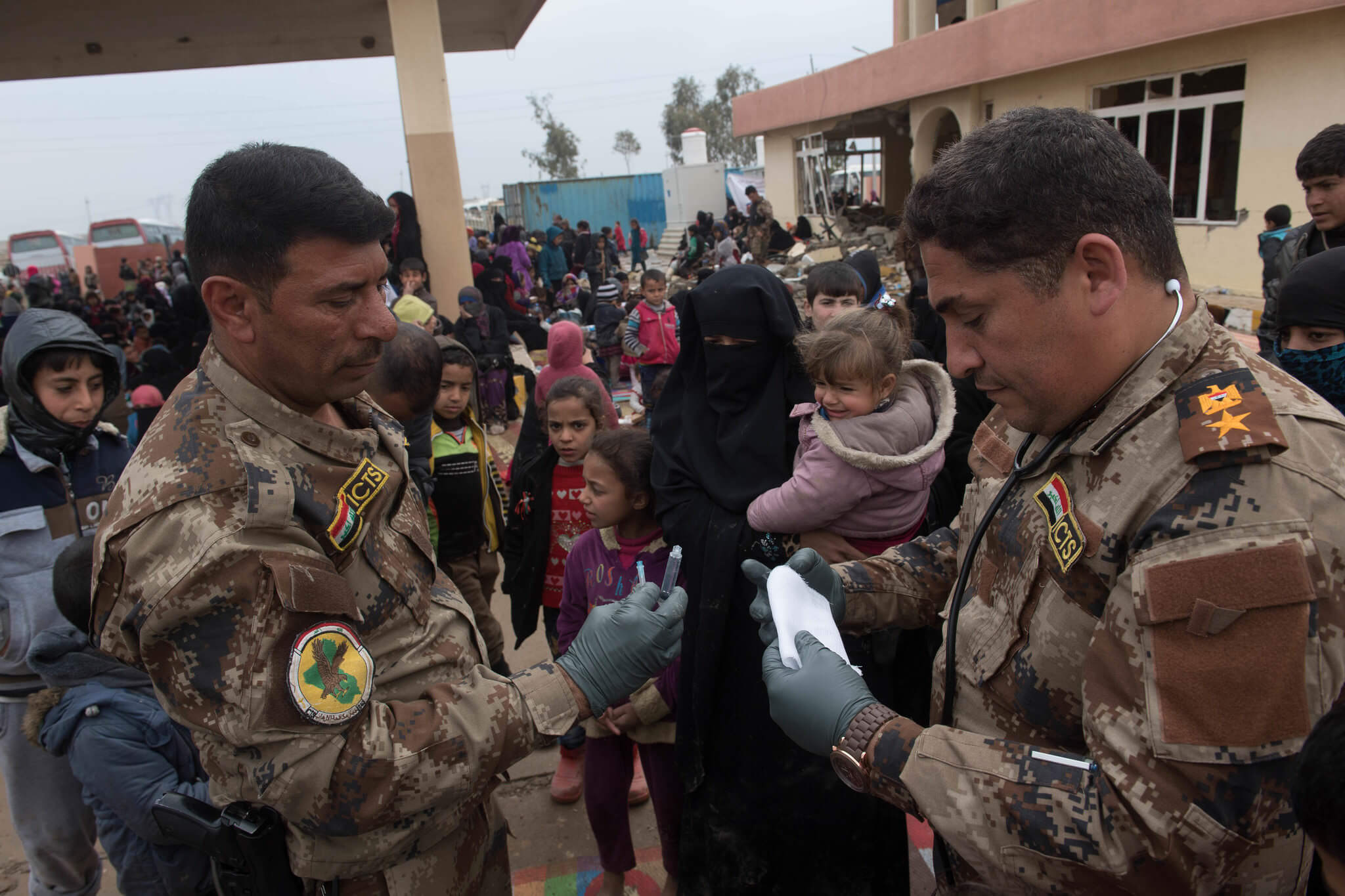 Iraqi Counter Terrorism Service surgeon Lt. Col. Hayder Al Sudani, right, and Sallah Kahdum, treat patients at a processing station for internally displaced people near Mosul, Iraq, on March 3, 2017.