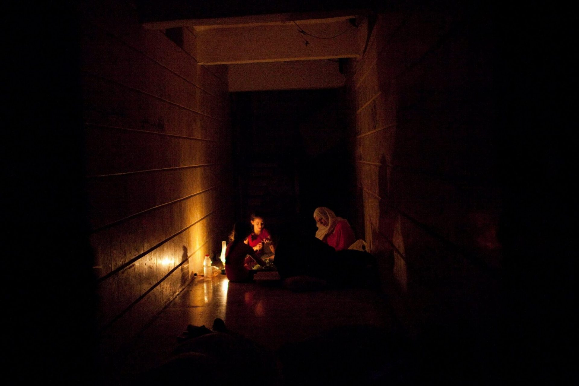 A family takes shelter in the hallway of their apartment building in the Salaheddin neighborhood of Aleppo, Syria, on Thursday, August 2, 2012 during a bout of heavy shelling that hits the area frequently from Assad army positions. Salaheddin, the most restive neighborhood that saw the biggest anti-government demonstrations throughout the revolution has been hit hard, is almost cleared of all its residents while mostly Free Syrian Army fighters remain.