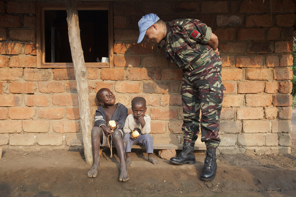 A UN peacekeeper on foot patrol in Dungu, a town in the extreme north of Oriental Province, near the border with South Sudan, stops to chat with local children. Image courtesy of MONUSCO/Sylvain Liechti