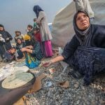 A woman, displaced by fighting in Mosul, bakes bread on an improvised stove in Jeddah displacement camp, Qayyarah, Iraq, in November 2016.